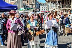 women in old costumes eating food in Europe