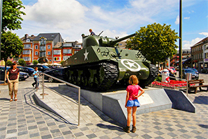 a girl looking at an army tank in Belgium