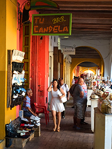 a woman walking along a colonnade in Cartagena