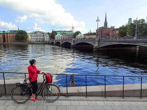 a woman on a bike near a harbor in Sweden