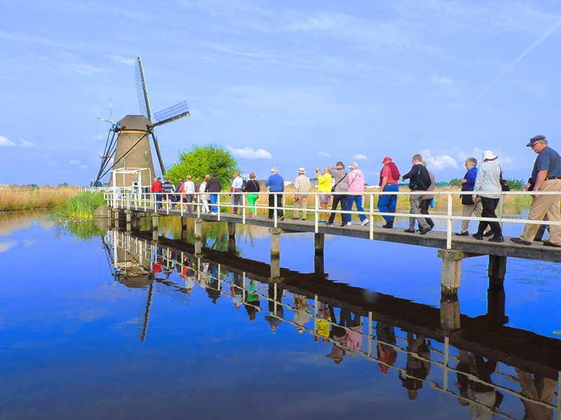 people walking on a bridge to a windmill on a Viking cruise
