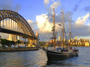 a boat in the harbor by a bridge in Sydney