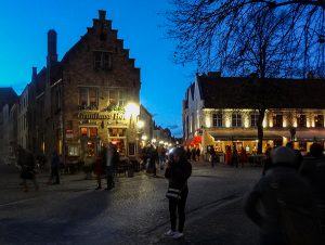 people on a street in the evening in Bruges