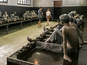 people walking through a prison museum in Hanoi