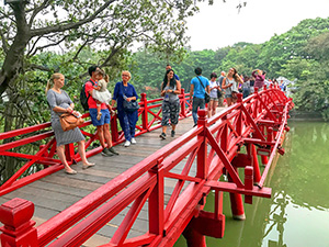 people on a red-painted bridge in Hanoi