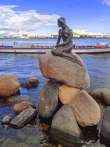 a statue on teh water's edge in Scandinavia