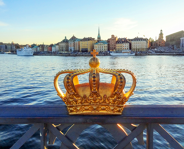a crown on a fence by a harbor in Scandinavia
