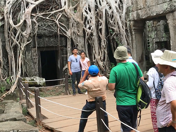 people by the roots of the Tomb Raider Tree in Ta Prohm, Cambodia