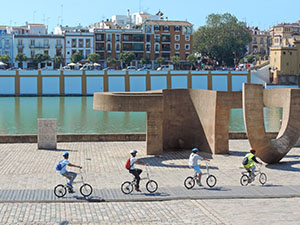 bicyclists along a river in Seville