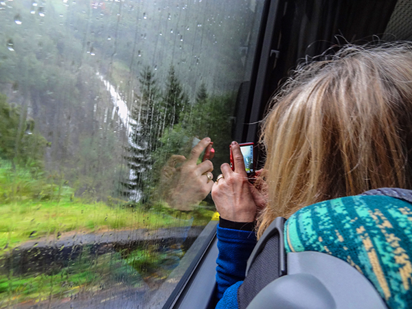 woman taking a photo out a train window in Norway in Scandinavia