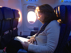 a woman reading a book on a plane - save airfare