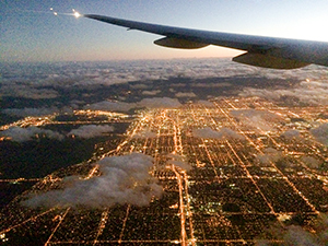 flying over a city at night - save airfare
