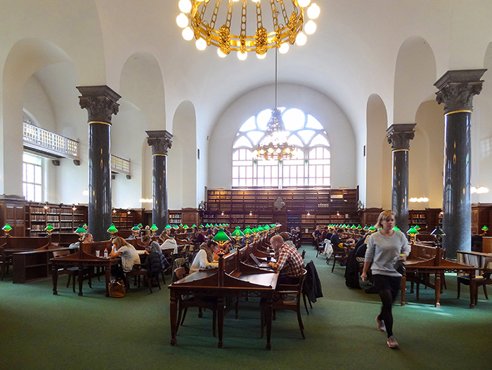 people sitting at tables in a library in Copenhagen, Denmark