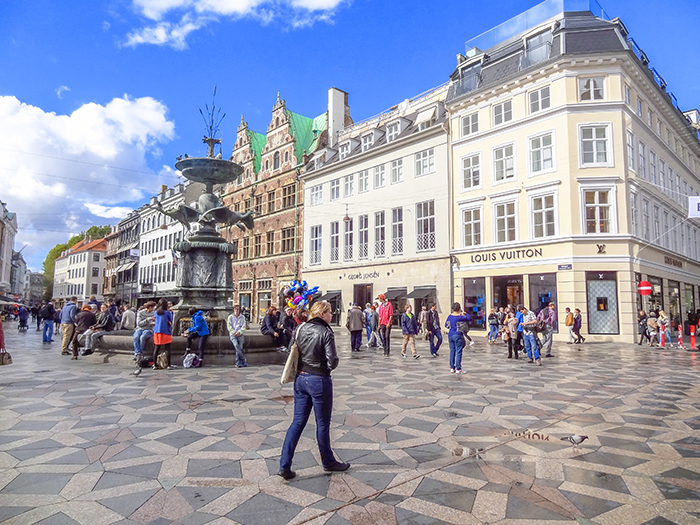 people walking across a plaza in Copenhagen, Denmark