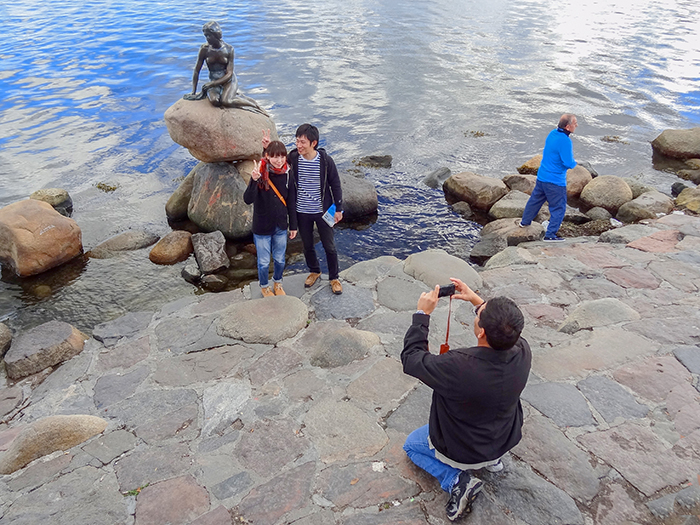 man taking a photo by a statues in Copenhagen, Denmark