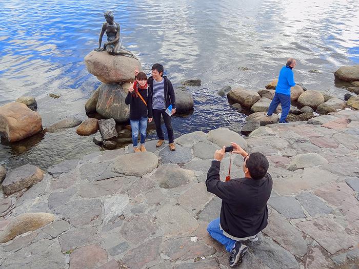 man taking a photo by a statues in Copenhagen, Denmark