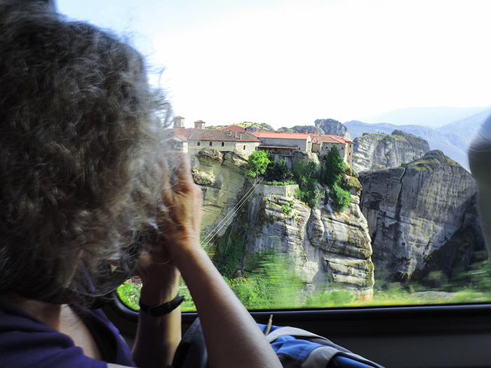 woman taking photos from a car window in Meteora