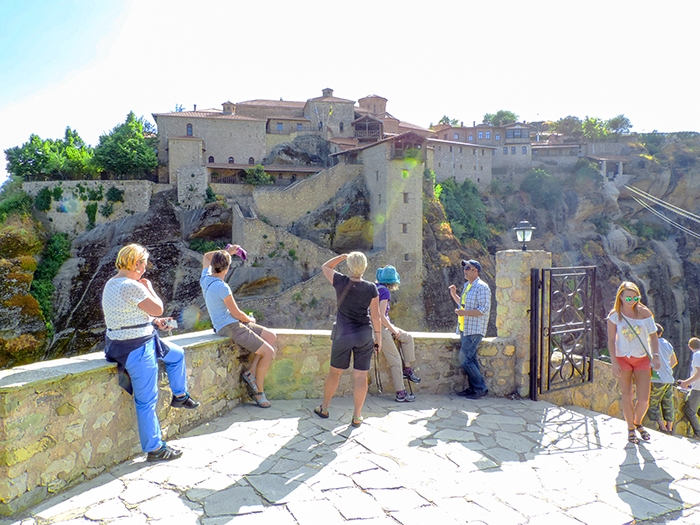 people looking at an ancient building in Meteora