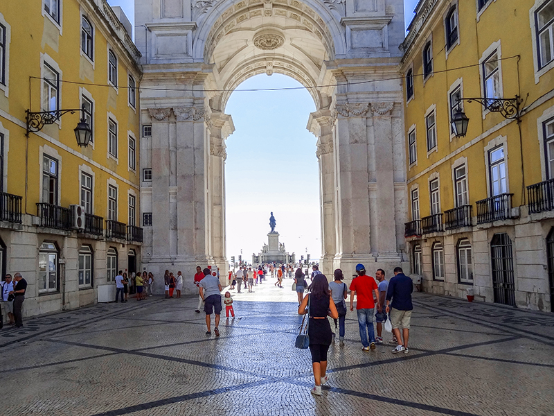 people wallikng towards a large arch in Lisbon, Portugal