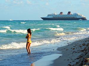 a woman on teh beach watchign an ocea liner deprt in South Beach Miami