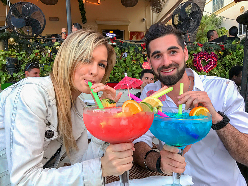 couple drinking large colorful drinls in South Beach Miami