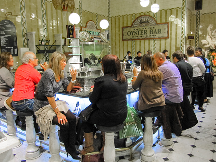 people at a food hall counter in Harrods