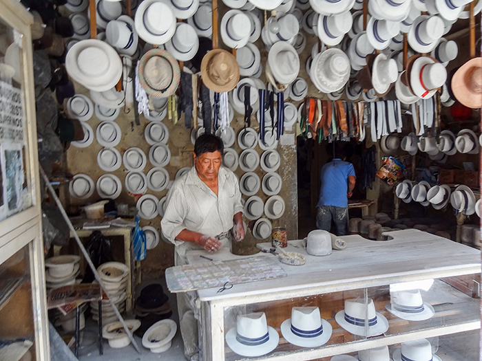 man standing under hanging hats in Cuenca, Ecuador