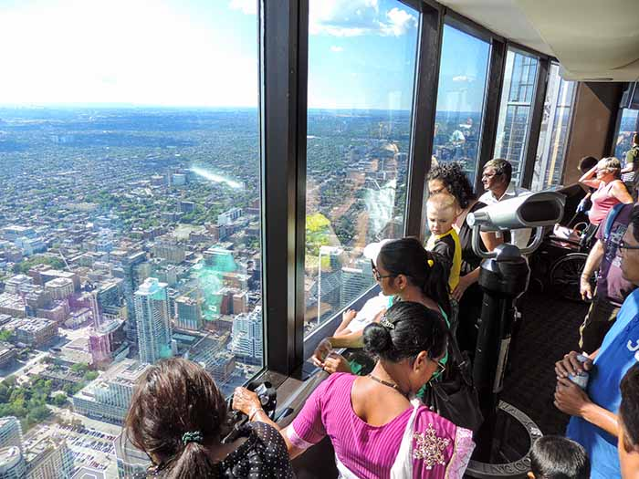 people looking out the window of a tall tower in Toronto