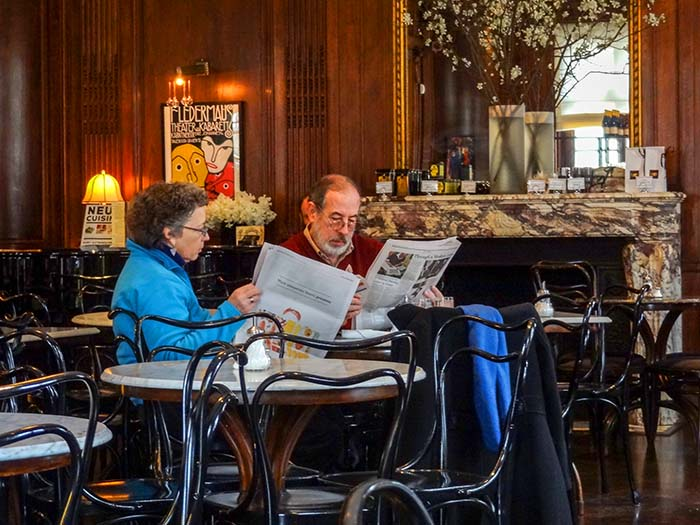 couple reading newspapers in one of the best restaurants in New York City museums