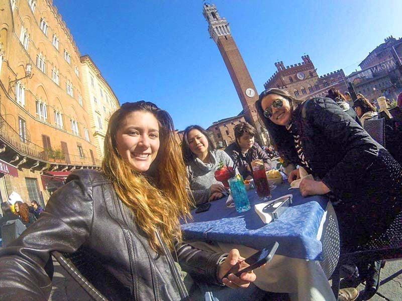 3 students at a cafe table in Italy study abroad