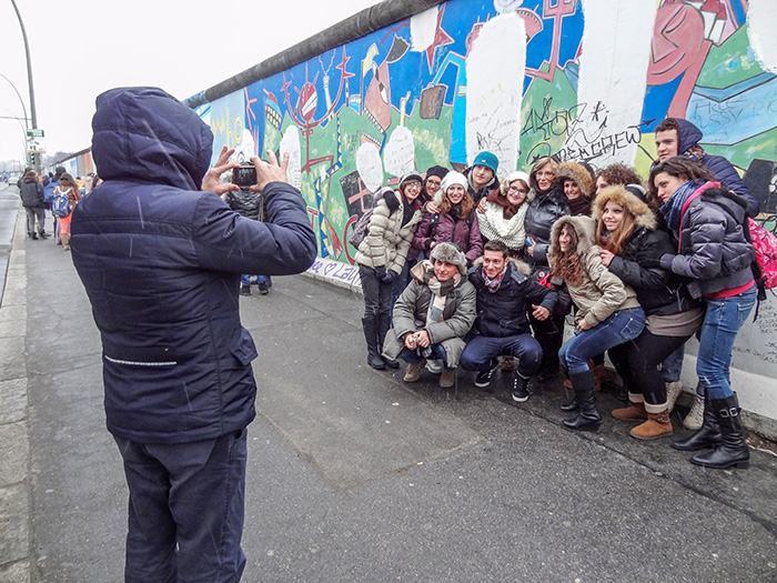 A group having their photo taken at teh Berlin Wall, one of The Best Things To Do In Berlin, Germany