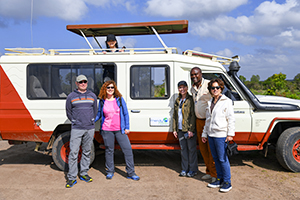 people standing by a van on safari in kenya