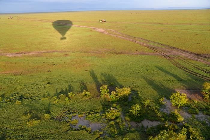 shadow of a hot-air balloon over Maasai Mara on safari in kenya