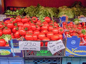 tomatoes in a marketan artist paiting a harbor scene in Cinque Terre Italy