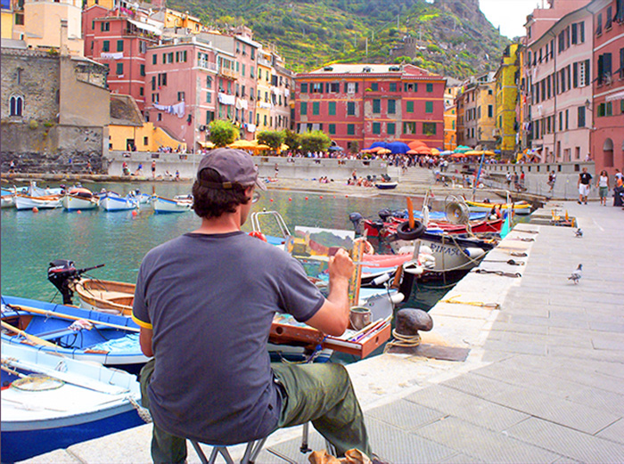 an artist paiting a harbor scene in Cinque Terre Italy
