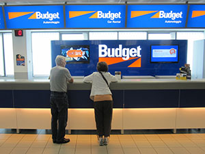 couple at a car rental counter budget travel
