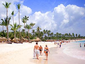 a couple walking on a beach - travel insurance
