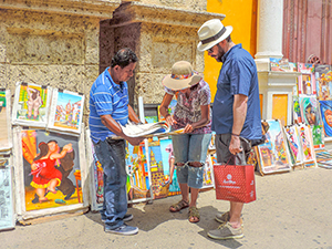 people with a sidewalk artist - travel insurance