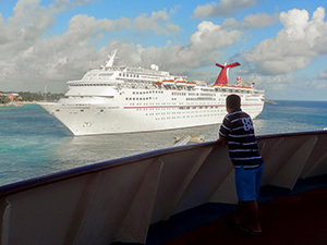 man looking at a cruise ship - travel insurance