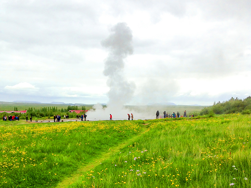 people by a geyser on an Iceland tour