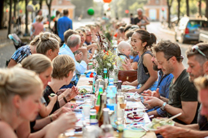 people dining at a long table at a food festival in Europe