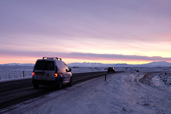cars on road at sunrise - Iceland ice caves