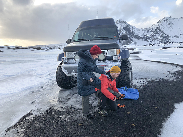 attaching crampons to boots - Iceland ice caves