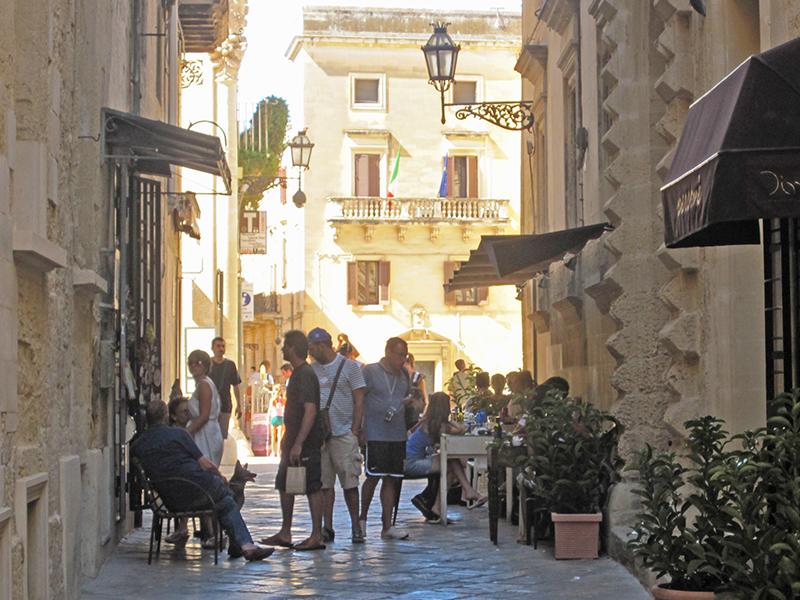 people on a sidestreet in an old Italian town in Puglia