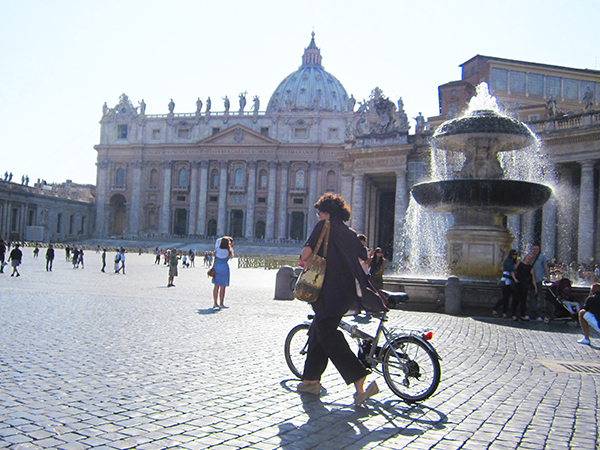 woman walking a bike in St peter's Square top 10 in Italy