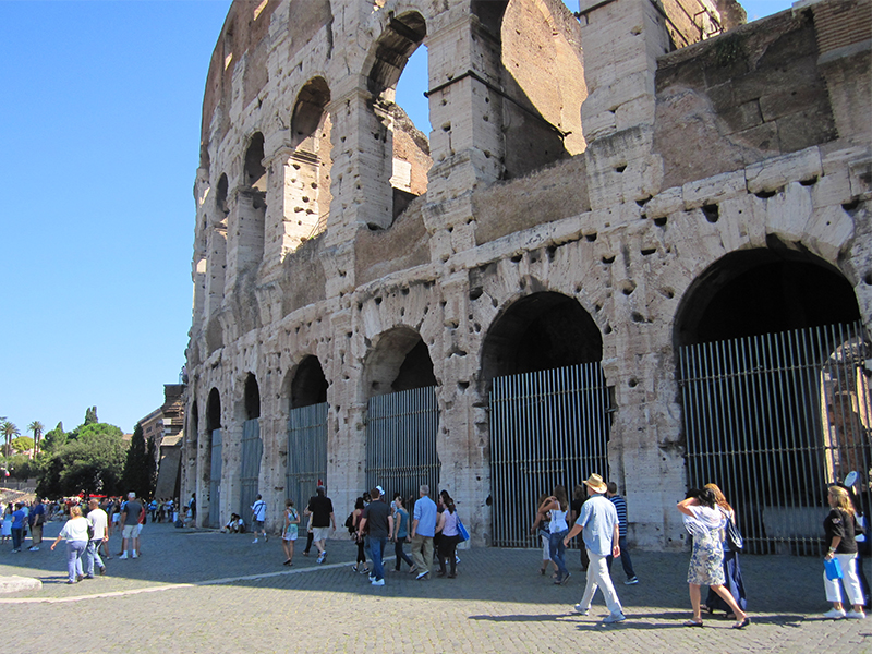 people walking outside Rome's Colosseum, one of the best places to visit in Italy