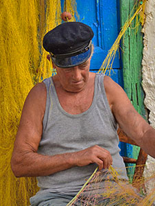 a fisherman tending his nets on a Greek Island