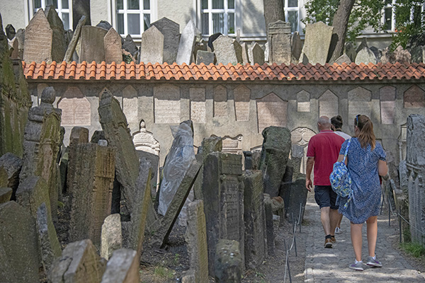 people walking through an old cemetery in Prague - airport in Prague