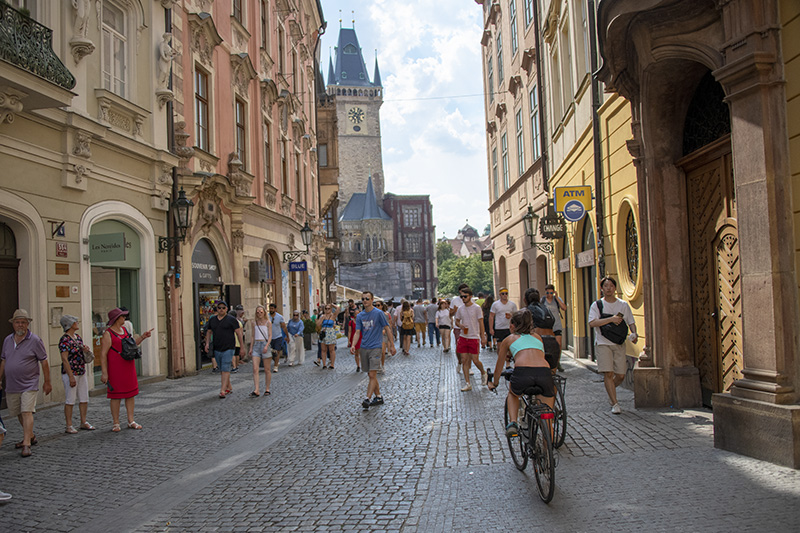 a bicyclist on a street with old buildings - things to do in Prague