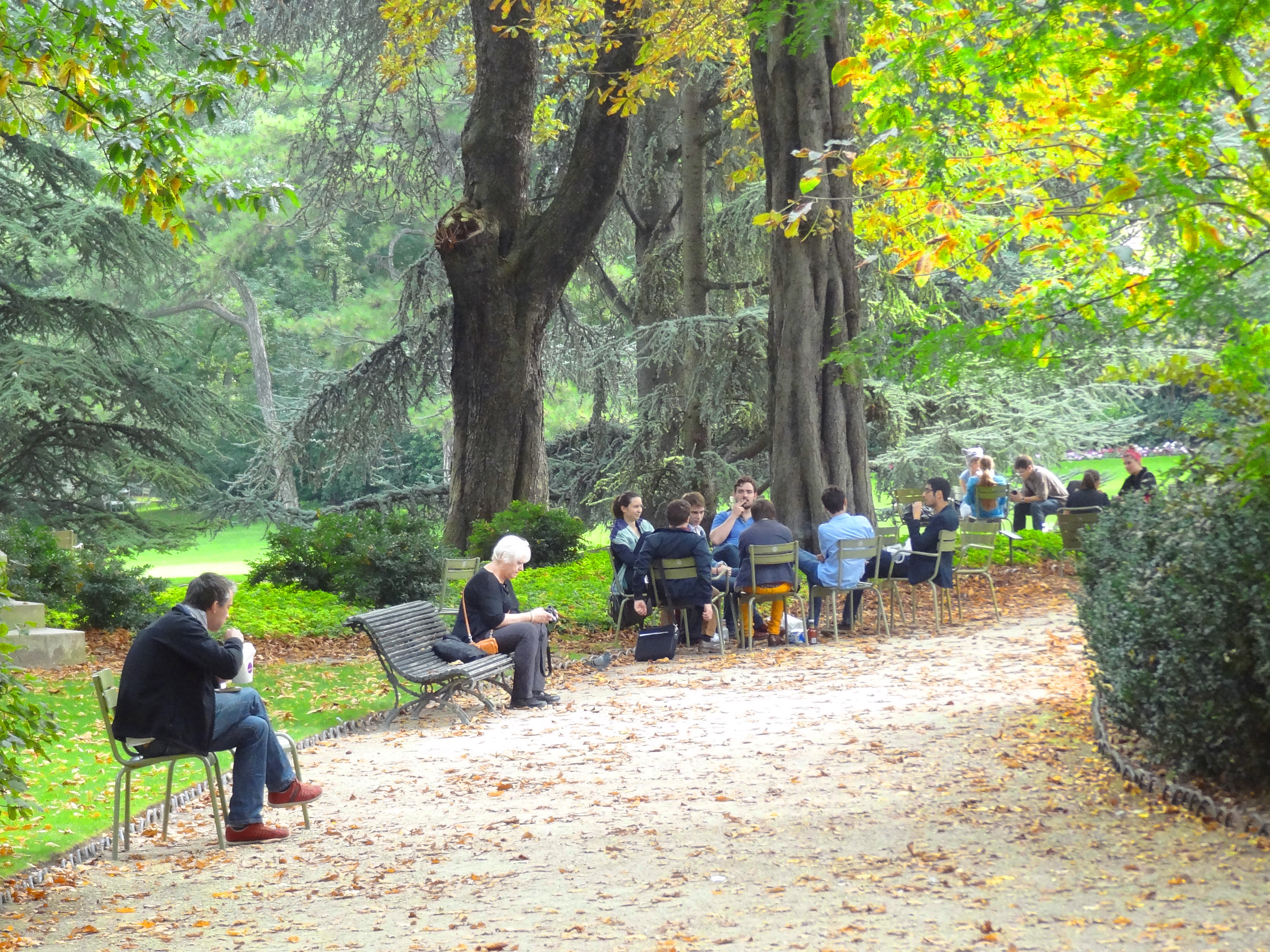 people sitting on a park path - paris itineraries and paris map